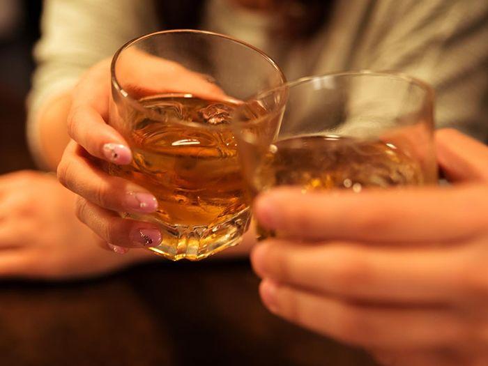 ロックグラスを手に乾杯する男女