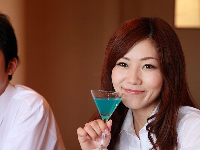 カクテルグラスを片手に微笑む女性