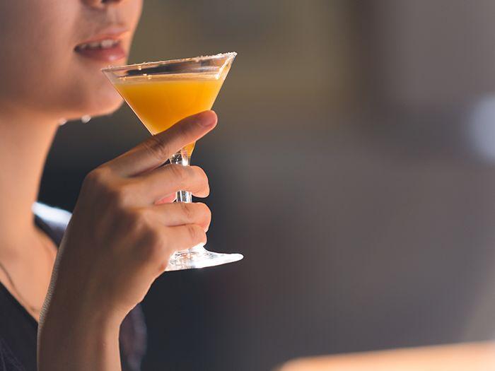 カクテルグラスを口元に寄せる女性