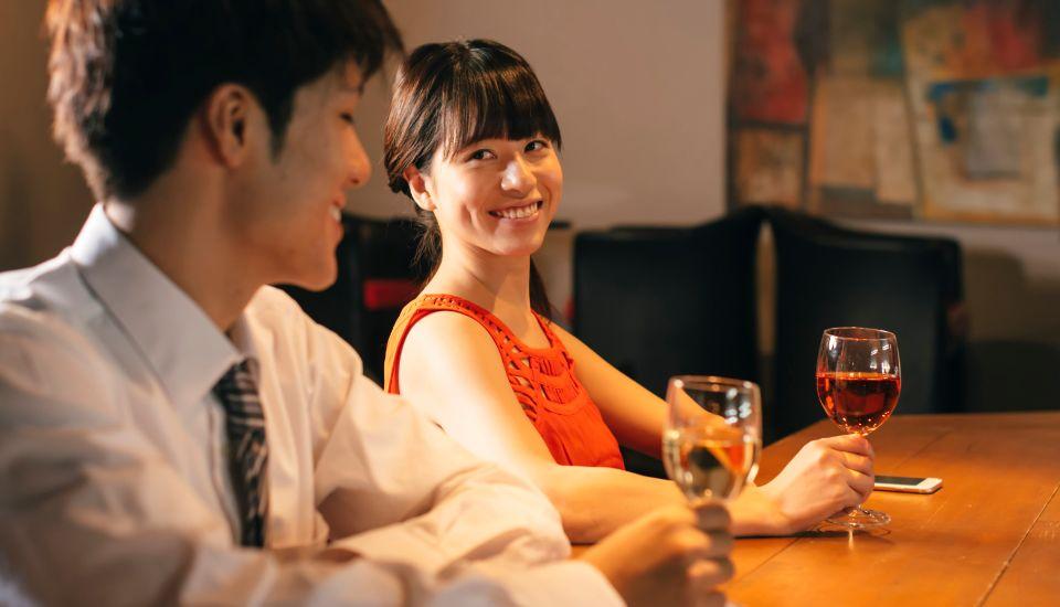 グラスワインを手に談笑する男女
